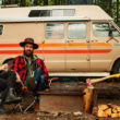 couple sitting in front of camper van with campfire and chopped wood with axe - guide to van life